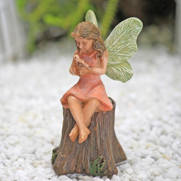 My little friend fairy sitting on tree stump with tiny bird for 2 little birds sat on my window