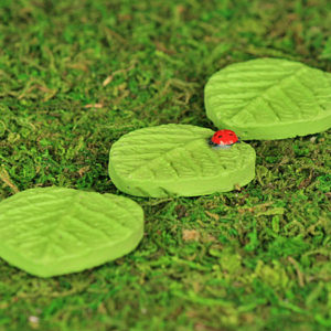 A set of three leaf shaped stepping stones, one has a tiny little ladybird. Hand made from clay.